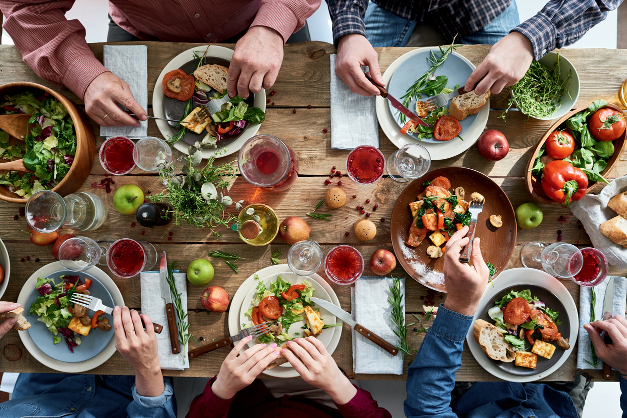 Directly above view of unrecognizable friends eating together at diner party