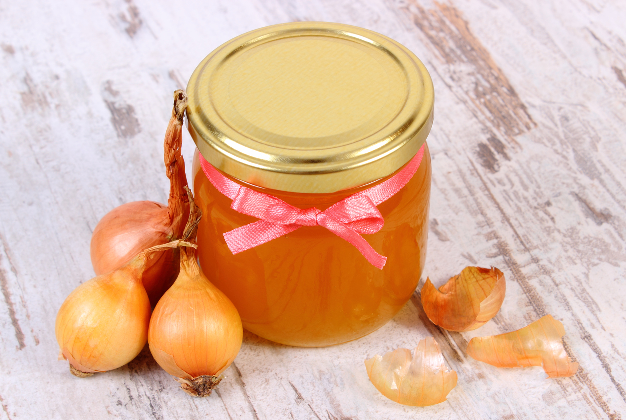 Fresh organic honey in glass jar and onions on old rustic wooden background, healthy nutrition, strengthening immunity and treatment of colds and flu