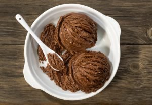 Chocolate ice cream in white bowl with a spoon, on a wooden plank.
